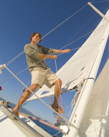 Low angle view of a young man standing on a sailboat and pulling a rope